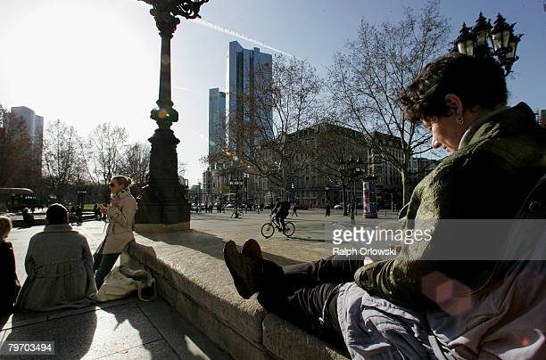 A woman reads a book while she sunbathes outdoors at Alte Oper on February 11 2008 in Frankfurt Germany Warm weather brought many people outdoors at...