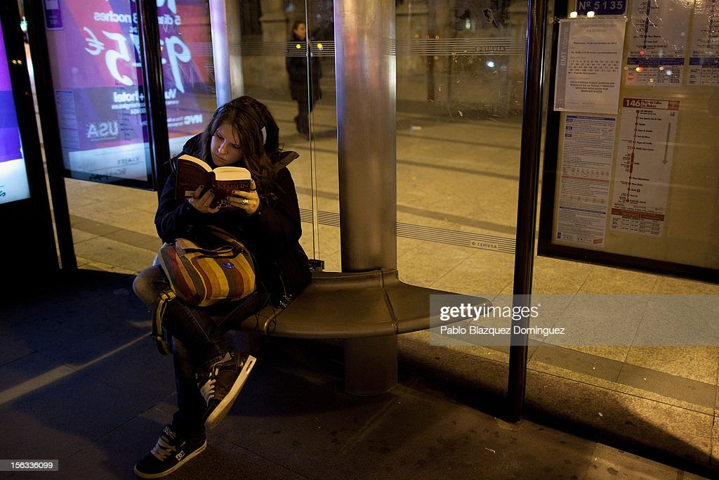 A woman reads a book while waiting for a bus on November 13, 2012 in Madrid, Spain. Spain's trade unions have called a general strike for November 14, the second general strike during Mariano Rajoy's presidency. Protestors from social movements are expected to join striking public sector workers to protest against austerity cuts and labour reforms. Spain's unemployment rate has now reached 25 per cent.