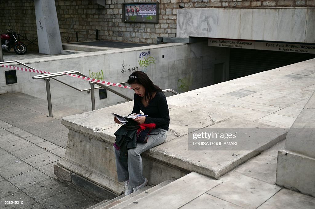 A woman reads a city map next to a closed metro station in Athens on May 6, 2016, during a 48-hours public transport strike. Greece's labour unions stage a two-day general strike to protest against controversial government plans to overhaul pensions and increase taxes to meet demands of its bailout creditors. / AFP / LOUISA