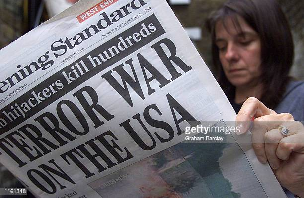 A woman reads a copy of an evening newspaper reporting the terrorist attacks on the United States on an underground train September 11 2001 in London