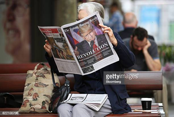 A woman reads a copy of the Sydney Morning Herald newspaper featuring a picture of US Presidentelect Donald Trump on its front page in the central...