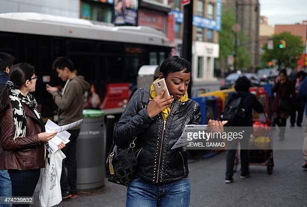 A woman reads a flyer about health concerns labor practices regulations and wages at nail salons she received from a volunteer outside a subway...