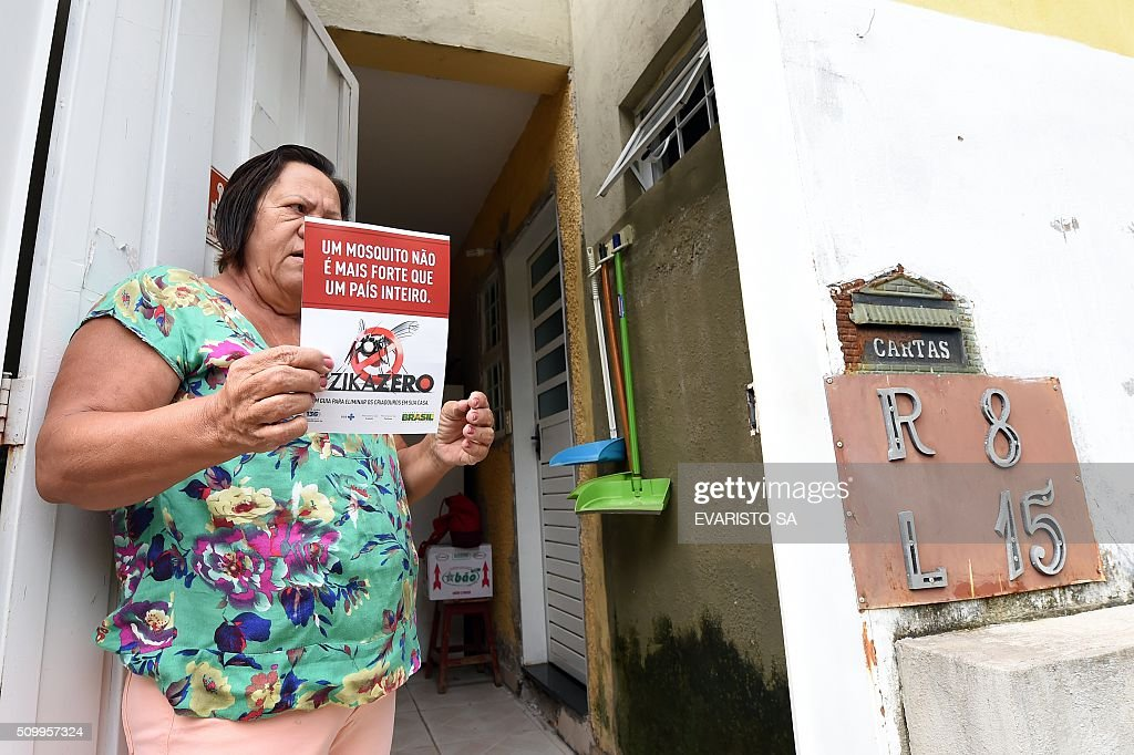 A woman reads a flyer left at her house as part of an awareness campaign to fight the Aedes aegypti mosquito in the Metropitana neighbourhood in Brasilia, Brazil, during the day of national mobilization against the mosquito that transmits dengue and chikungunya fever and zika virus, on February 13, 2016. Some 220,000 members of the armed forces have been deployed to visit 3 million homes throughout Brazil during the day. AFP PHOTO/EVARISTO SA / AFP / EVARISTO SA
