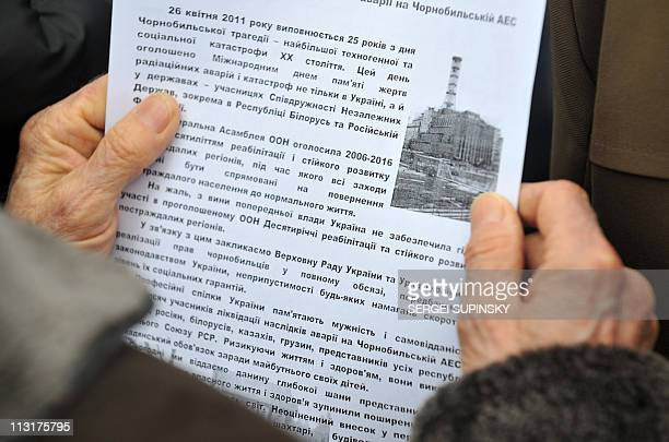 A woman reads a leaflets showing tge 4th block of Chernobyl's Nuclear Power Plant covered with the 'sarcophagus' during a rally organized by the...