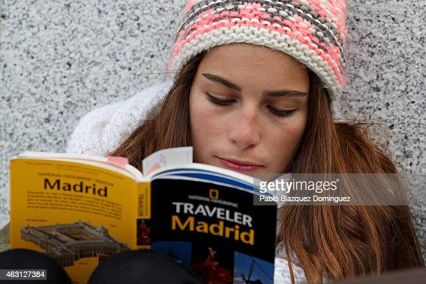 A woman reads a Madrid traveler book as she queues to enter the Prado Museum on February 10 2015 in Madrid Spain The Prado Museum is running an...