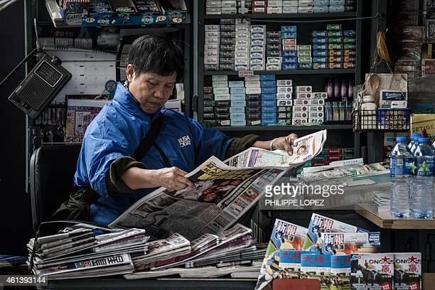 A woman reads a newspaper at a kiosk in Hong Kong on January 12 2015 Firebomb attacks on the Hong Kong home and office of prodemocracy newspaper...