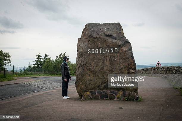A woman reads a plack on a stone that marks the Scotish/English border in the border regions of Scotland on June 12th 2014 Views and snapshots from...