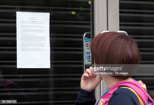 A woman reads a press statement on the shutter of Peats World of Electronics in Parnell Street store Dublin One of Ireland's bestknown electronics...