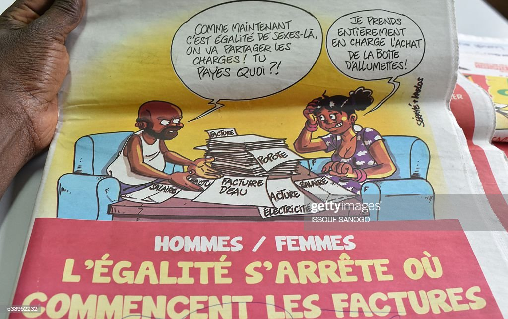 A woman reads a satirical newspaper made of cartoons in Abidjan on May 24, 2016. Press cartoonist took part in an exhibition at the French Institute gathering 20 years of cartoons in the media on the history of Ivory Coast, until the post-electoral crisis of 2010-2011 that killed 3,000 people. / AFP / ISSOUF