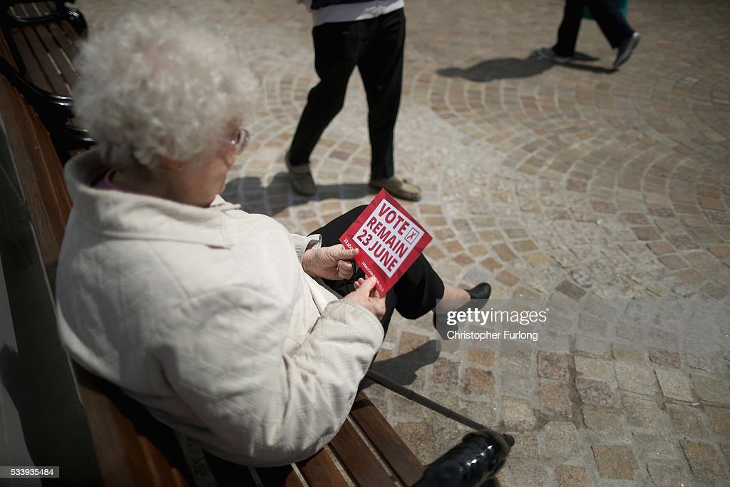 A woman reads a 'Vote Remain' leaflet as former Labour leader Ed Miliband campaigns for remain votes while touring with the 'Labour In Battle Bus' at St John's Square on May 24, 2016 in Blackpool, England. The 'Labour In' campaign is hoping to persuade UK citizens to stay in the European Union when they vote in the EU Referendum on the June 23.