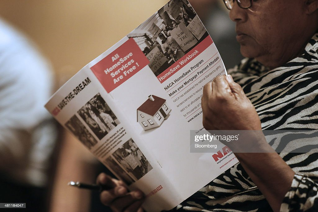 A woman reads a workbook in order to receive help with a home loan modification during the Neighborhood Assistance Corporation of America (NACA) event in Los Angeles, California, U.S., on Friday, March 28, 2014. Fed buying of the securities that helped spur a housing recovery is poised to fall below growth in the $5.5 trillion government-backed market as soon as May, Nomura Holdings Inc. said. Last year, the Fed added twice as much of the debt as was created, suppressing yields that guide mortgage interest rates. Photographer: Patrick T. Fallon/Bloomberg via Getty Images