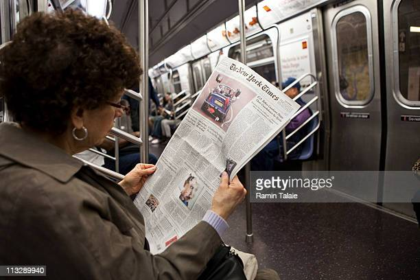 A woman reads about the royal wedding of TRH Prince William Duke of Cambridge and Catherine Duchess of Cambridge in The New York Times newspaper on...
