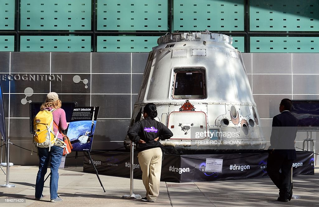 A woman reads about the SpaceX Dragon spacecraft on exhibit at the California Science Center during a media preview ahead of the opening of Endeavour Fest, commemorating the one-year anniversary of the Space Shuttle Endeavour's arrival in Los Angeles, on October 11, 2013 in California. While visitors to the three-day exhibition will also see a SpaceX Dragon spacecraft as well as the west coast launch of the Red Bull Stratos Exhibit, the lack of funding to NASA due to the government shutdown precludes their participation in Endeavour Fest, as NASA will not be able to provide exhibits or displays for the event and the NASA scientist presentations will be cancelled AFP PHOTO/Frederic J. BROWN