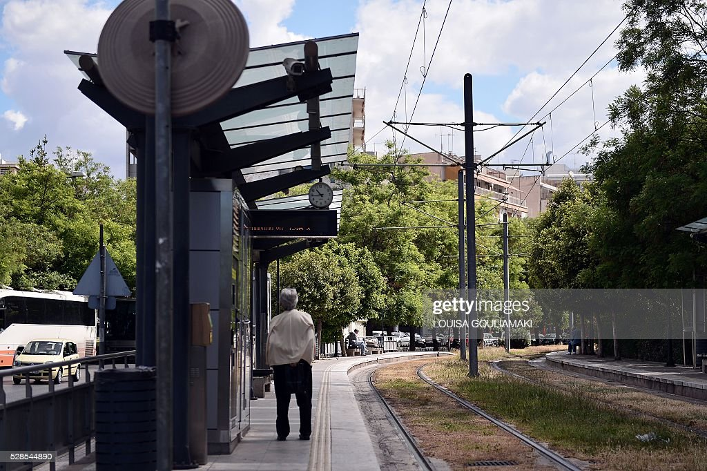 A woman reads an announcement informing about 48-hours strike as she stands at a closed tram station in Athens, on May 6, 2016. Greece's labour unions stage a two-day general strike to protest against controversial government plans to overhaul pensions and increase taxes to meet demands of its bailout creditors. / AFP / LOUISA