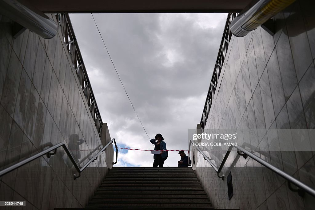 A woman reads an announcement informing about a 48-hours strike as she stands at a closed metro station in Athens, on May 6, 2016. Greece's labour unions stage a two-day general strike to protest against controversial government plans to overhaul pensions and increase taxes to meet demands of its bailout creditors. / AFP / LOUISA