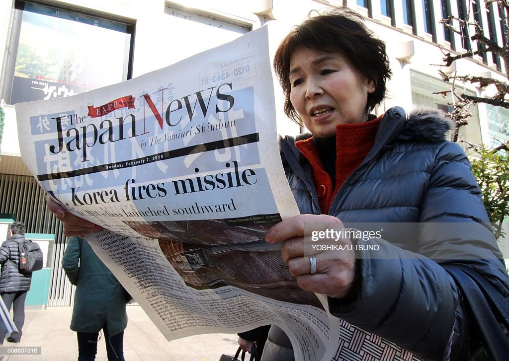 A woman reads an extra edition newspapers in Tokyo which report about North Korea's rocket launch on February 7, 2016. North Korea launched a long-range rocket on February 7, violating UN resolutions and doubling down against an international community already determined to punish Pyongyang for a nuclear test last month. AFP PHOTO / Yoshikazu TSUNO / AFP / YOSHIKAZU TSUNO