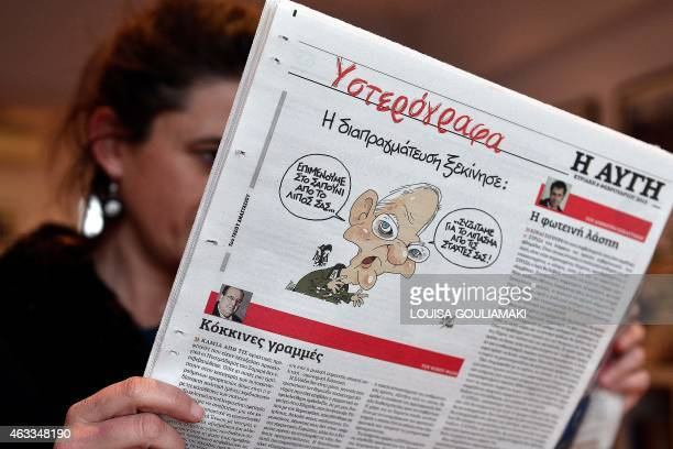 A woman reads 'Avgi ' leftist newspaper in Athens with a cartoon depicting Germany's finance minister in a Wehrmacht uniform saying 'we insist on the...