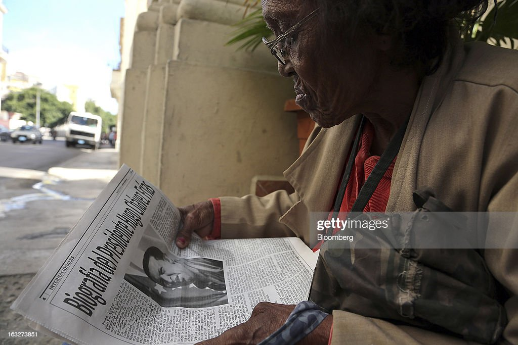 A woman reads coverage about the death of Venezuelan President Hugo Chavez in the Communist party newspaper, La Granma, in Havana, Cuba on Wednesday, March 6, 2013. Cuba's government praised Chavez for uniting the people of Latin America and pledged loyalty to the continuation of his Bolivarian Revolution, according to the statement in the state-run Granma website. Photographer: Noah Friedman-Rudovsky/Bloomberg via Getty Images