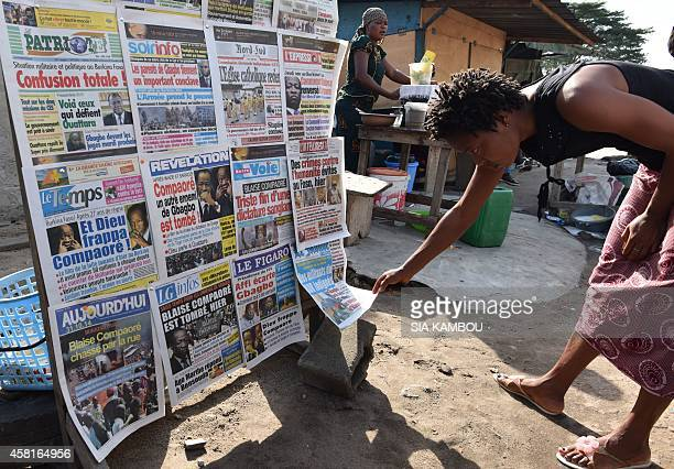 A woman reads daily newspapers leading with stories about the recent events in Burkina Faso in Abidjan on October 31 2014 Burkina Faso's President...