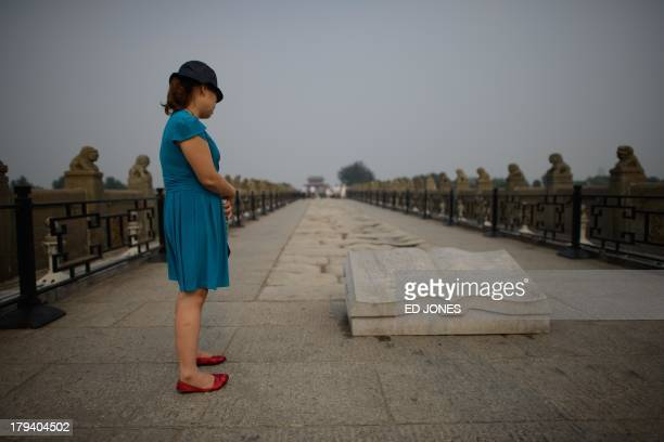 A woman reads from an inscription on the Marco Polo bridge or Lugouqiao in west Beijing on September 3 2013 The bridge was the scene of the...