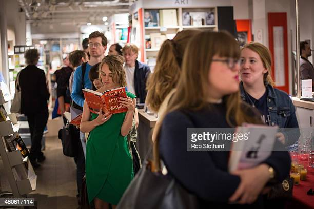 A woman reads 'Go Set A Watchman' by Harper Lee whilst queuing to buy it shortly after midnight at Foyles book shop on July 14 2015 in London England...