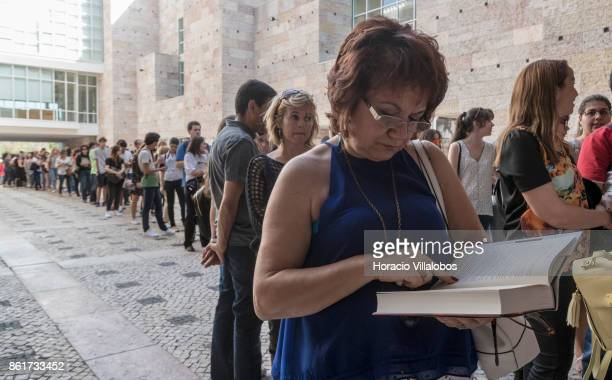 A woman reads her copy of the Portuguese edition of 'Origin' Dan Brown last book while queueing to attend its presentation by the author at Centro...