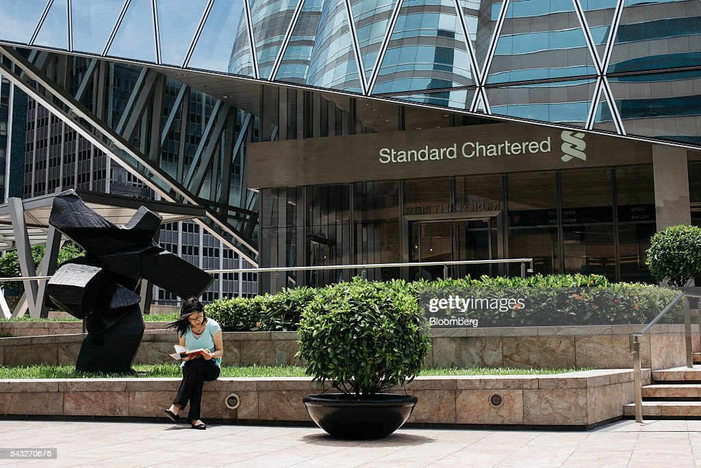 A woman reads in front of a Standard Chartered Plc bank branch in the Central district of Hong Kong, China, on Monday, June 27, 2016. The aftershocks of the U.K.'s vote to leave the European Union continued to reverberate across financial markets, with the pound extending its selloff near a 31-year low and European equities dropping to levels last seen in February. Asian shares rebounded with commodities. Photographer: Anthony Kwan/Bloomberg via Getty Images
