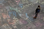 A woman reads messages written on the ground at a makeshift memorial Place de la Bourse following attacks in Brussels on March 22 2016 Airlines...