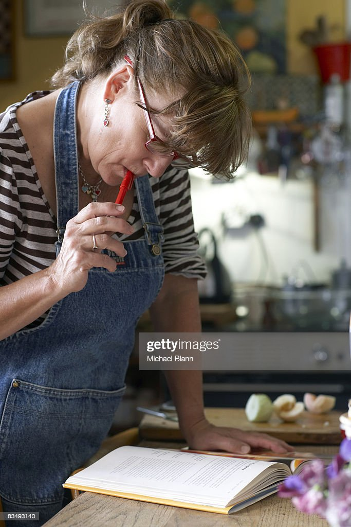 Woman reads recipe book in kitchen
