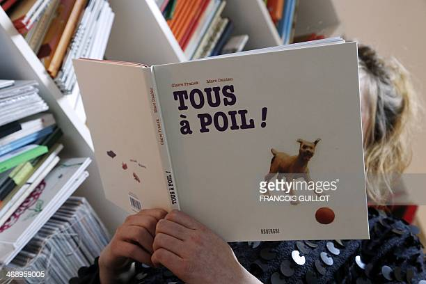 A woman reads the children's book 'Tous a poil' or 'Everyone naked' coauthored by Claire Franek and Marc Daniau and illustrated by Daniau at the...