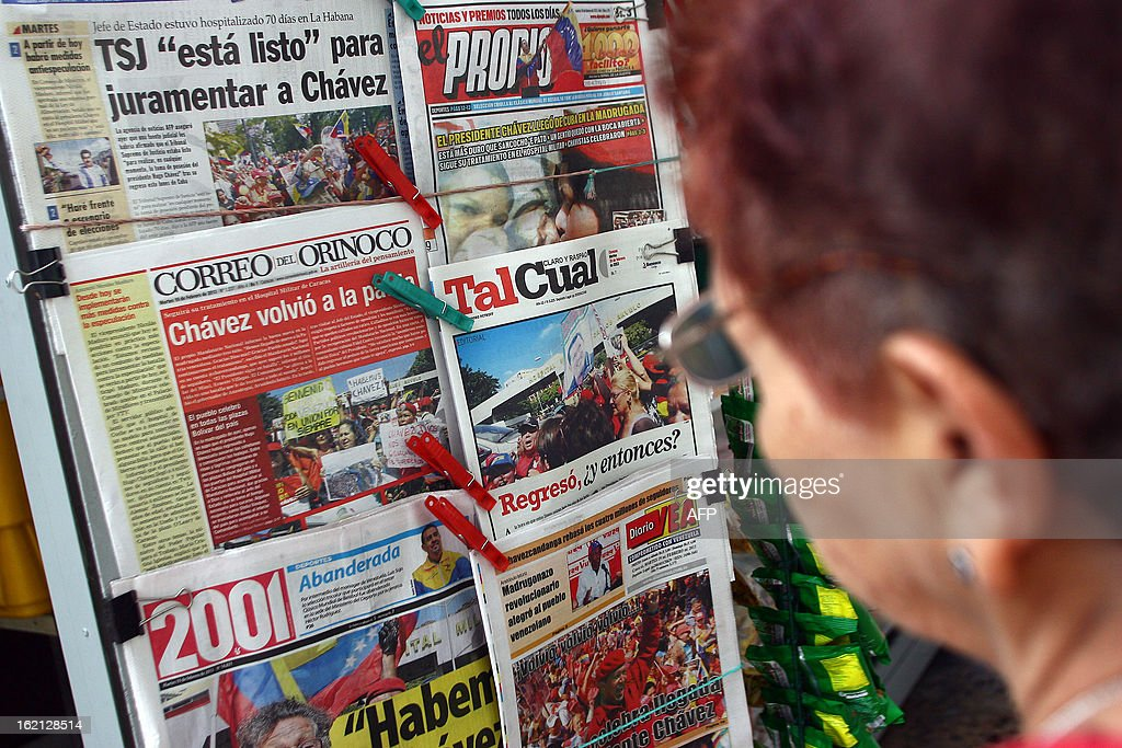 A woman reads the headlines of newspapers with news about the arrival of Venezuelan President Hugo Chavez at the country, in Caracas on February 19, 2013. President Hugo Chavez returned to Venezuela early on February 18 after spending more than two months in Cuba for cancer surgery and treatment, announcing his surprise homecoming via Twitter.