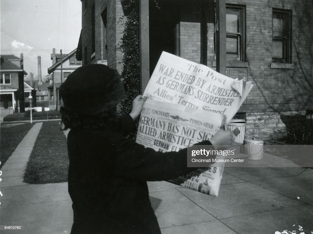 A woman reads the headlines of the local papers 'The Cincinnati Times Star' and 'The Post' proclaiming that an armistice has been signed ending the...