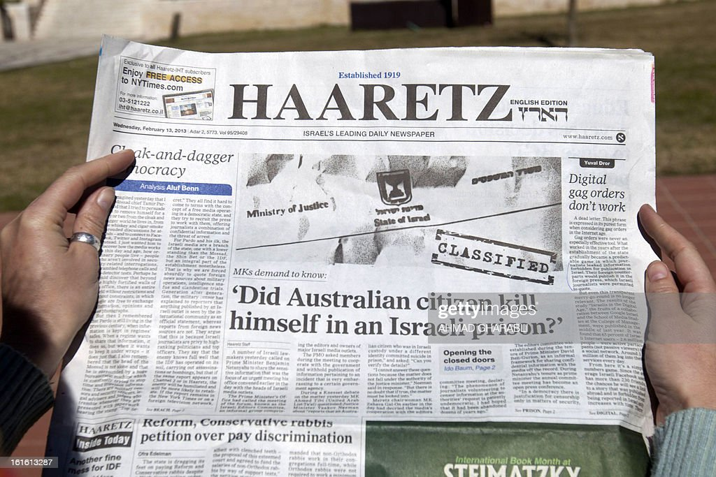 A woman reads the latest issue of the Haaretz daily newspaper whose cover page raises a question on the alleged suicide of an Australian prisoner with ties to Mossad on February 13, 2013 in Jerusalem. Twenty-four hours after the emergence of an explosive investigative report by Australia's ABC news, the Israeli censor moved to ease the total blackout on coverage of the incident, allowing the local press to publish details from the report.