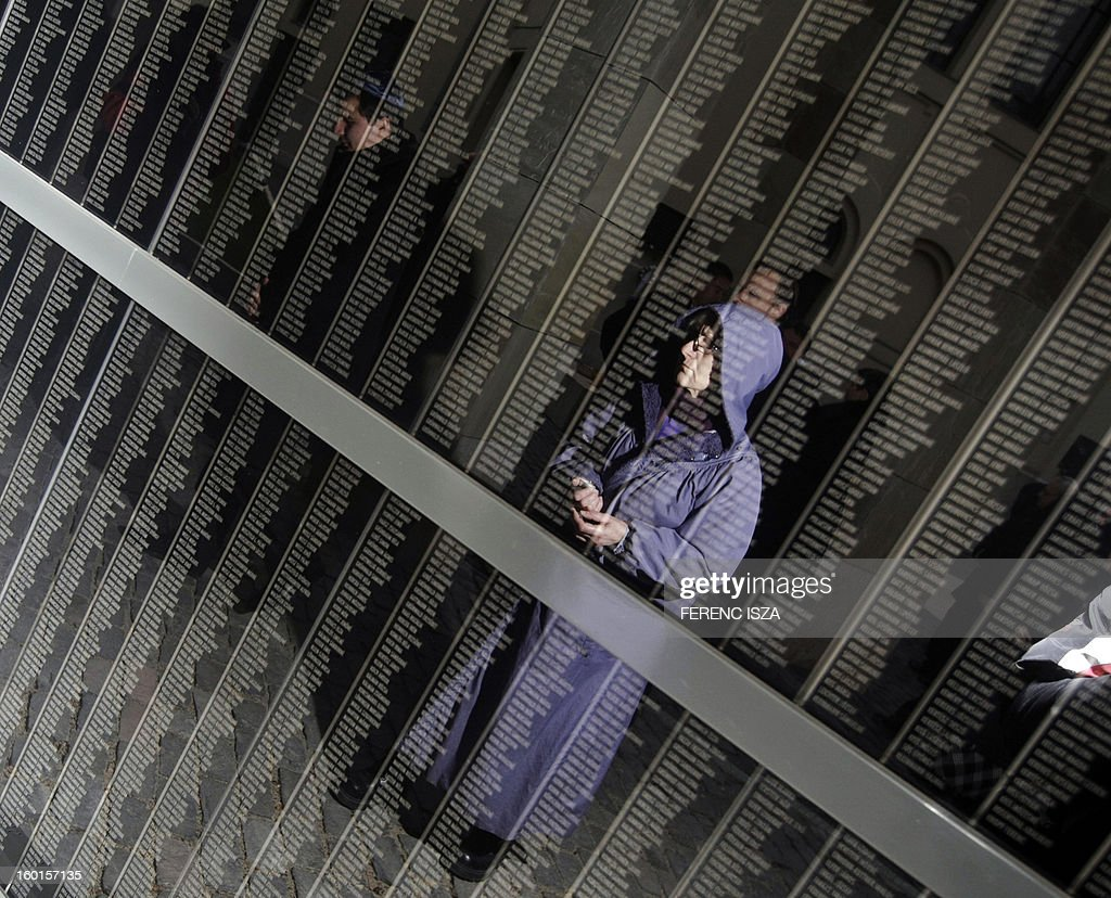A woman reads the name on the wall of victims at the Holocaust Museum in Budapest, Hungary on January 27, 2013, the International Holocaust Memorial Day to commemorate the victims of the Nazi regime.