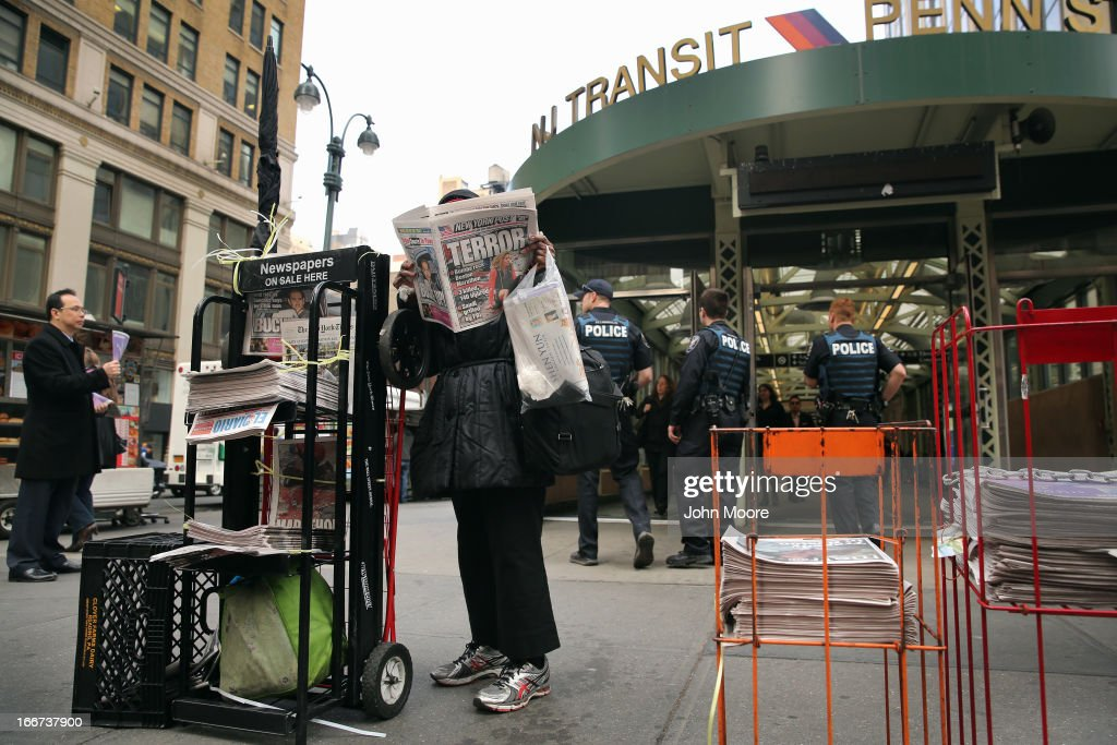 A woman reads the New York Post as police stand guard outside Penn Station on April 16, 2013 in New York City. Police were out in force throughout New York, a day after explosions near the finish line of the Boston Marathon killed 3 people and wounded more than 170 others.