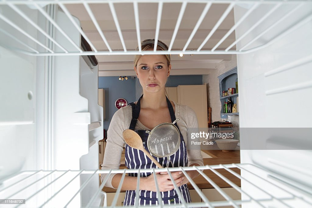 woman ready to cook looking into empty fridge : Stock Photo