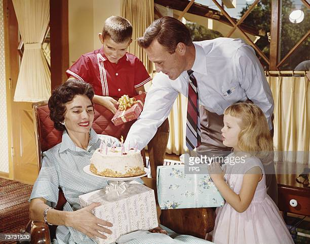 A woman receives a birthday cake and gifts from her family circa 1960