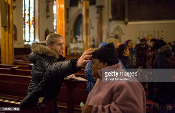 A woman receives a blessing from Father Johannes while waiting in line to receive donated items from Catholic Charities of Brooklyn and Queens in the...