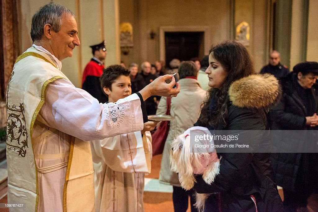A woman receives communion as she holds her dog during a traditional mass for the blessing of animals at the Sant'Eusebio church on January 20, 2013 in Rome, Italy. Every year during the feast of St. Anthony the Abbot animals are blessed in countries around the world.