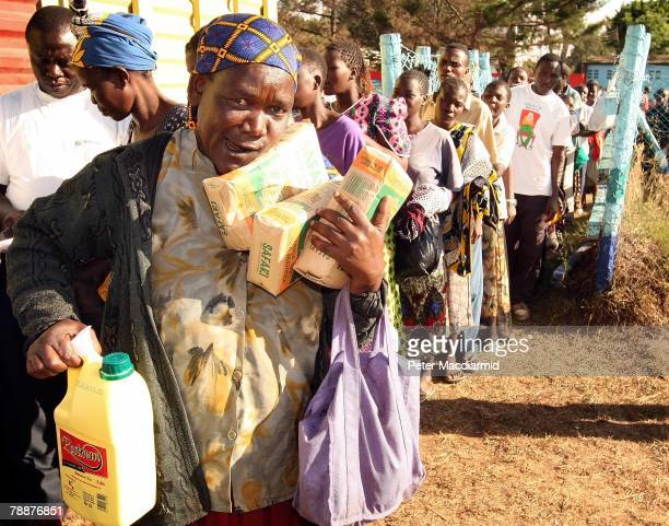 A woman receives food aid at the agricultural showground on January 10 2008 in Nairobi Kenya Talks hosted by Ghanaian President John Kufuor to bring...