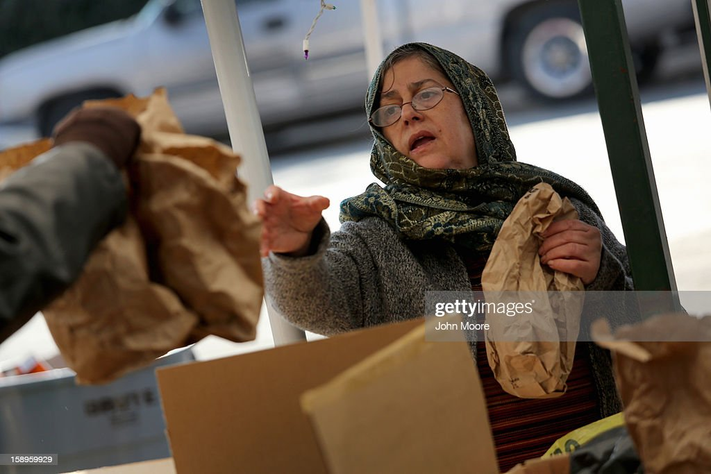 A woman receives food at a Superstorm Sandy aid distribution center on January 4, 2013 in the Midland Beach area of the Staten Island borough of New York City. More than two months after the storm, Congress passed legislation today that will provide $9.7 billion to cover insurance claims filed by people whose homes were damaged or destroyed by Sandy.