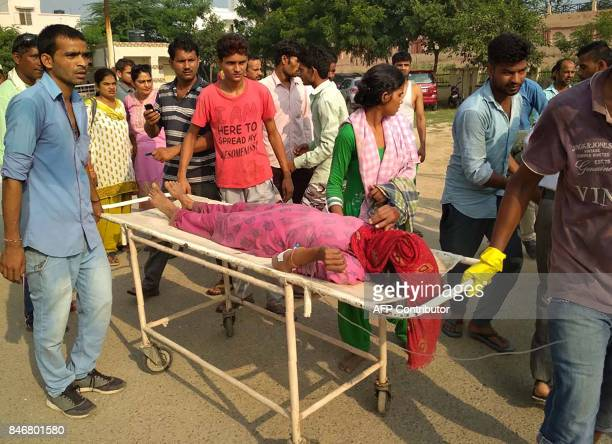 A woman receives medical care on a stretcher after a boat capsized on the Yamuna river near the city of Baghpat in the northern state of Uttar...