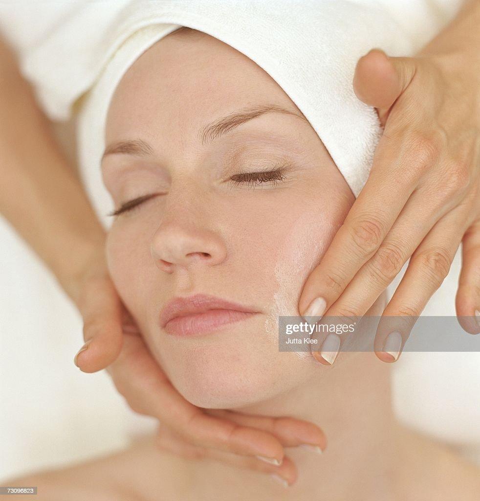 Woman receiving a facial treatment at a beauty spa : Stock Photo