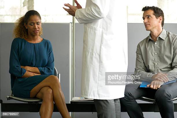 Woman receiving bad news from doctor in waiting room