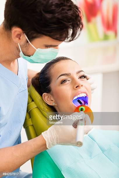 Woman receiving dental filling drying procedure