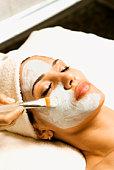 Woman receiving facial treatment at spa