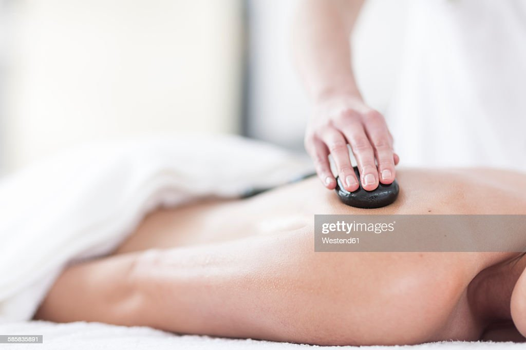 Woman receiving hot stone massage in a spa