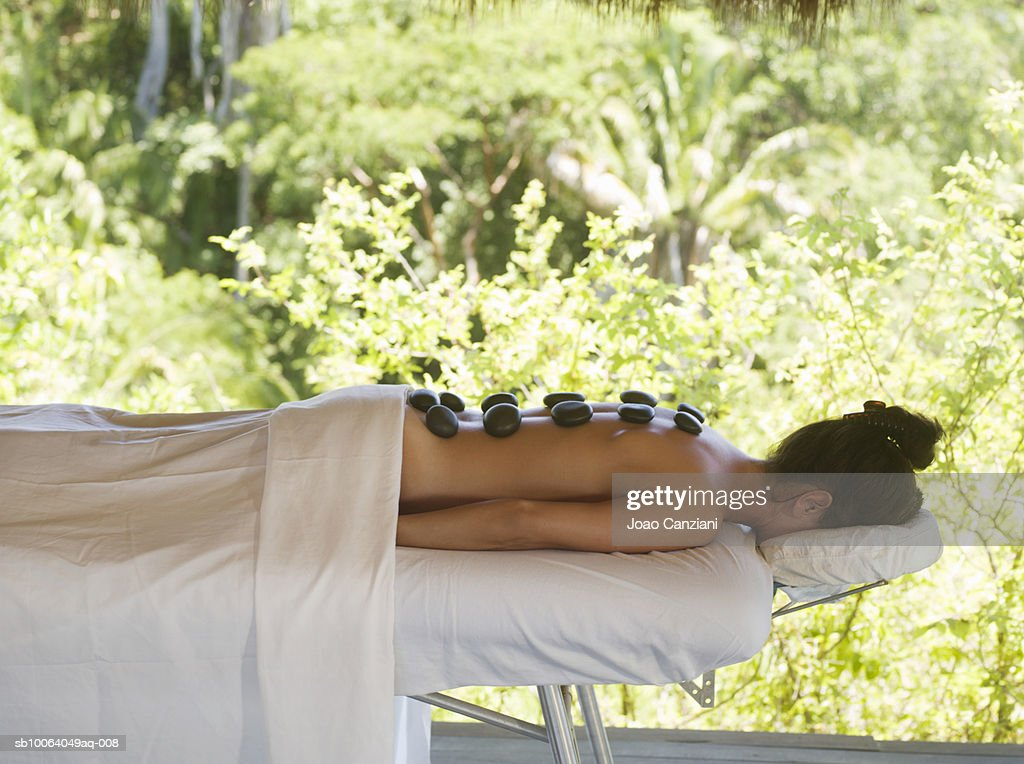 Woman receiving hot stone therapy lying down on massage bed, side view : Stock Photo