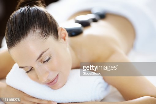 A woman receiving hot stone therapy : Stock Photo