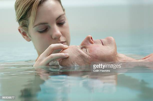Woman receiving massage in pool